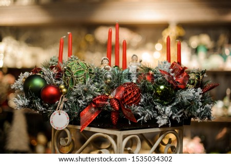 Huge christmas composition of snow covered fir-tree branches, candles, tapes, red and green toy balls and toy children in the blurred background of flower shop #1535034302