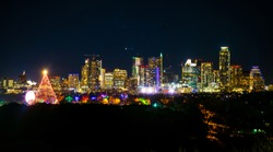 Huge Christmas tree lights up the night Austin Texas skyline cityscape at night with Trail of Lights Zilker Park Christmas festival event a colorful Christmas cheer light display