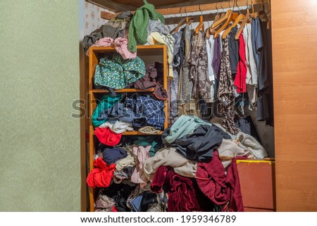 Huge closet filled with used clothes, sloppily shoved and hanging from shelves and hangers. Wardrobe mess. Wardrobe clutter. Foto stock ©