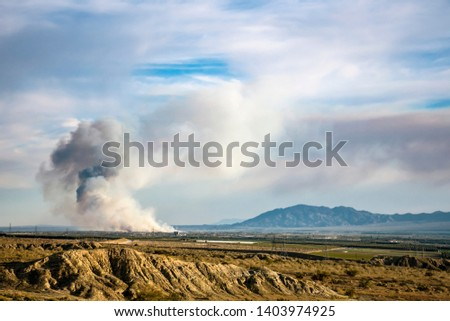 Huge cloud of smoke billows into sky from large brush fire on agriculture land. Land clearing project or explosion #1403974925