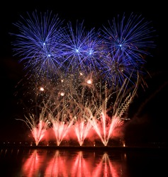 Huge colorful fireworks display with orange, blue and red streaks on the river bank