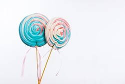 Huge colorful meringue on a stick like a popsicle (lollipop) on a white background isolated with copy space for message. Birthday candies for celebration. Sweet swirls or suckers for table decoration.