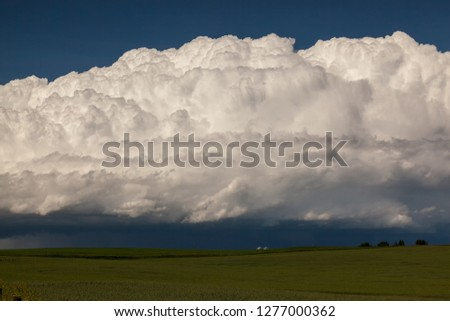 Huge Cumulonimbus cloud over farmland, farmland buildings and hay grass field in Okotoks Alberta #1277000362