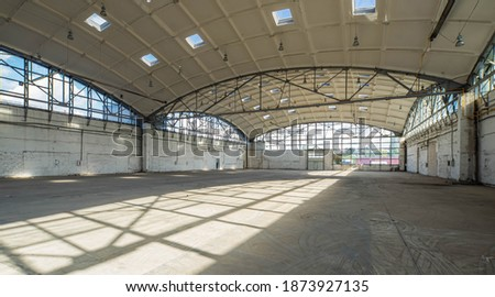 Huge empty industrial warehouse. White interior. Unique architecture. Hemispherical reinforced concrete load bearing roof with windows. Modern building. ストックフォト ©