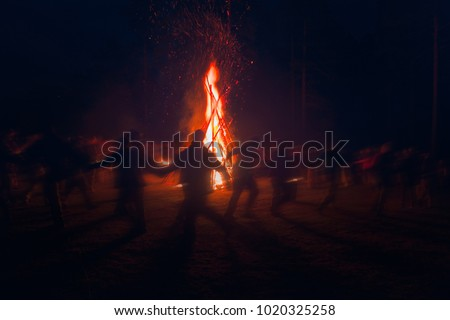 Huge fire at night and young people around. Pagan festival of Walpurgis night: bonfires, dancing wildly, demons, witches.