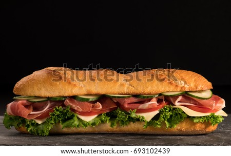 Huge fresh crispy baguette sandwich with meat, prosciutto, cheese, lettuce salad and vegetables. Close up. Black background. Space for text.