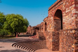 Huge gate structure at a fort made with red sandstone called Talaqi Darwaza near an amphitheatre with blue sky and green trees. A famous monument known as Purana Qila or Quila in Delhi, India.