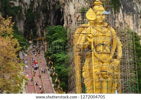 Huge gold statue of Lord Murugan under repair at Batu caves in Kuala Lumpur, Malaysia. The pic also shows devotees climbing up the stairs to Batu cave in the background. This is a Hindu worship temple