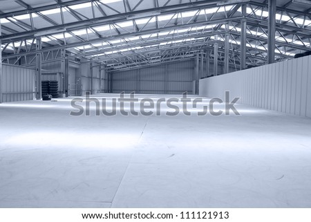 Huge gray empty and light warehouse with metal roof