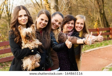 Huge group of women showing thumbs up for a cute little pet dog.