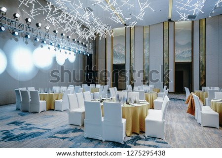 Huge Hall interior with red carpet and ceiling with lights in Hotel, elegant wedding reception table arrangement.