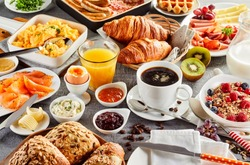 Huge healthy breakfast spread on a table with coffee, orange juice, fruit, muesli, smoked salmon, egg, croissants, meat and cheese