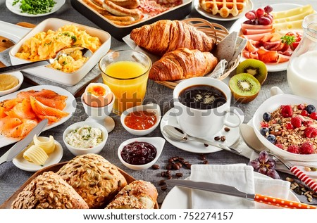 Huge healthy breakfast spread on a table with coffee, orange juice, fruit, muesli, smoked salmon, egg, croissants, meat and cheese #752274157