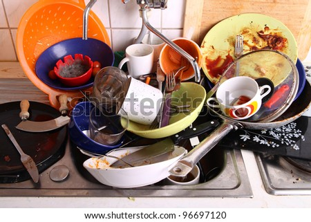 huge heap of dirty dishes waiting for the flatmate - stock photo