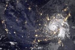 Huge hurricane over America, night photography. Lights of night cities and the eyes of the hurricane are clearly visible. Collage with abstract hurricane. Elements of this image furnished by NASA.
