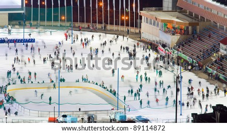 Huge ice skating rink with motion blurred large group of skating people. Kazakhstan, Medeo is an outdoor speed skating and bandy rink, located in a mountain valley - stock photo