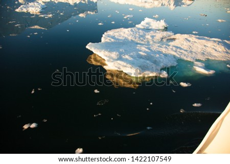Huge Icebergs with water reflection Ilulissat Greenland fjord under the midnight sun #1422107549