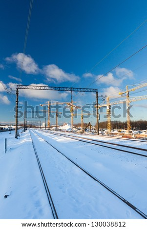 Huge industrial cranes on the construction site near rail road - winter season