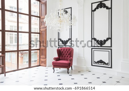 Huge luxury white hall with unique interior. Black and white tiles on the floor, white and black stucco on the walls, high fireplace with mirror mosaic, three-meter crystal chandelier and grand piano #691866514