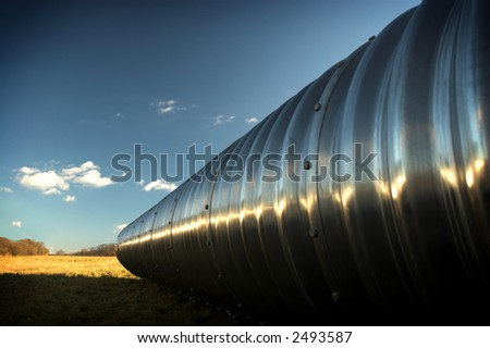 Huge metal pipe in a field