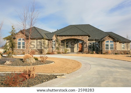 Huge modern one level house with long driveway and newspaper out front