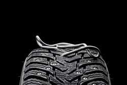 huge nail on a tyre over black background. studio shot. copy space. repair car tire concept. trouble on path conceptual.
