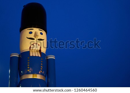 "huge nutcracker figur in traditional Ore Mountains style with blue ""jacket"" in front of a dark blue sky at a Christmas market #1260464560"