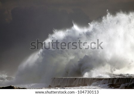 Huge ocean wave over the wall of the harbor of Vila do Conde, river Ave mouth, near Porto in the north of Portugal