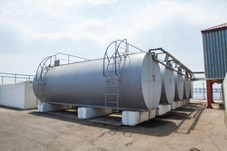 Huge oil, gas and liquid storage tanks in open air field at factory. Oil plant in the middle of Caspian Sea. Pipeline production and control valve for oil and gas process.