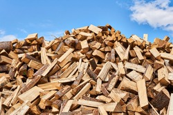 huge pile of firewood chocks against the sky close-up