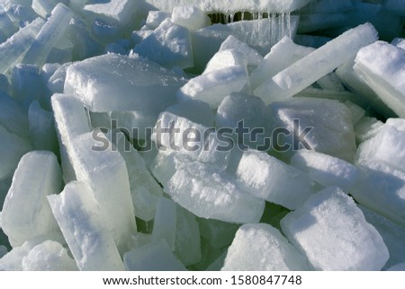 Huge pile of large ice blocks piled on each other on a sunny day