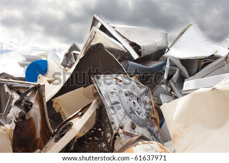 Huge pile of scrap metal with cloudy sky background