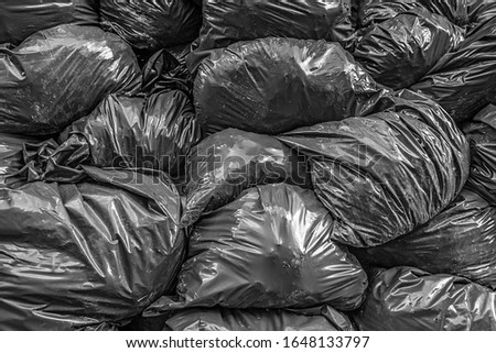 Huge pile of shiny black plastic bin bags filled with waste.