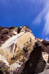Huge red and yellow rock cliff on red sand beach Santorini. Alien landscape.