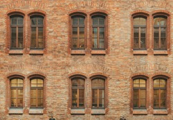 Huge red brick classic industrial building facade with multiple castle windows. Industrial background. Loft inspiration. Construction facade concept. Vintage effect.