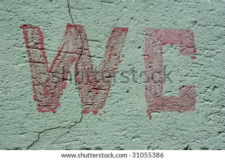 huge red letters painted on a wall spelling WC