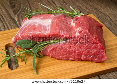 huge red meat chunk on wooden table