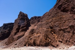 Huge red rock cliff on red sand beach Santorini. Alien landscape.
