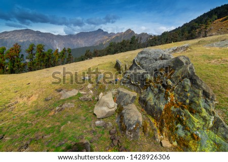 Huge rock on Bugyal, alpine pasture lands, or meadows, in higher elevation range of Himalayas in Uttarakhand, called nature's own gardens. View of Himalayas on Trekking route to Tunganath. #1428926306