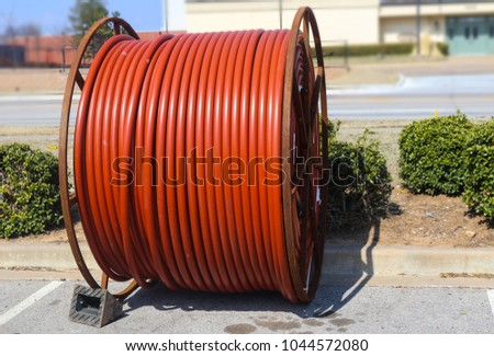 Huge roll of orange cable for underground cable installation sitting along a street #1044572080
