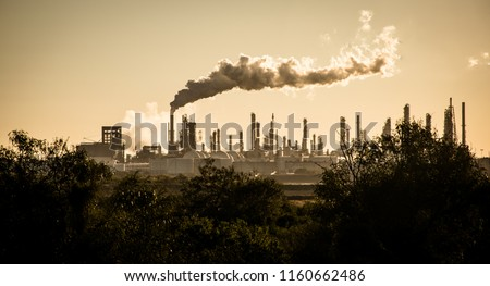 Huge smoke cloud rises from Oil petroleum refinery pollution smoke stack pouring carbon smog into the atmosphere climate change and global warming #1160662486