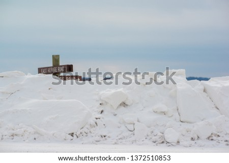 Huge snowy bank from plowed rural road with rural sign post barely visible above snow - in the Crex Meadows Wildlife Area in Northern Wisconsin #1372510853