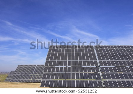 huge solar panels and blue cloudy sky