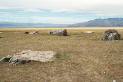 Huge stones among the steppe plain against the backdrop of a distant mountain range. Altai, Russia.