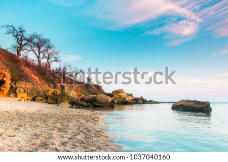 Huge stones in the water with bright blue and pink sunrise sky in the sea beach, Odessa, Ukraine #1037040160
