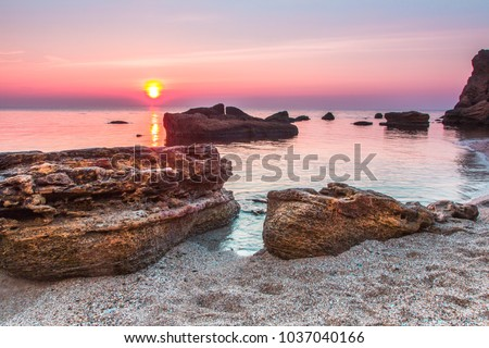Huge stones in the water with bright blue and pink sunrise sky in the sea beach, Odessa, Ukraine #1037040166
