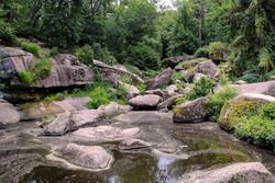 Huge stones over the pond on a background of green trees and bushes. Dendrological park Sofiyivka, Uman Ukraine.