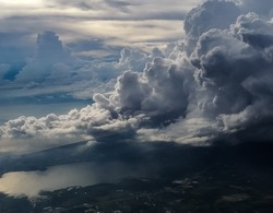 huge storm cloud, tower cumulus and cumulonimbus cloud, develop over sea and lake at dawn