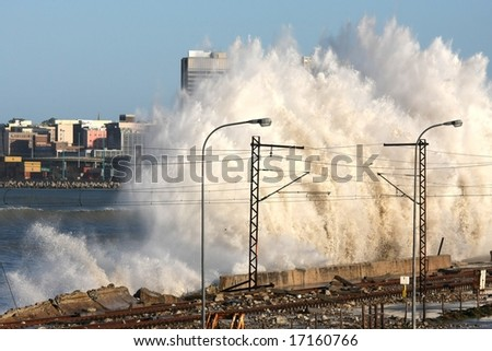 Huge storm waves slamming into a wall next to railway tracks