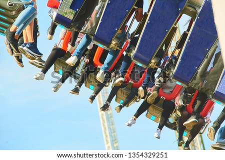 Huge swing in the entertainment center flying high in the air. People enjoying extreme adrenaline entertainment.